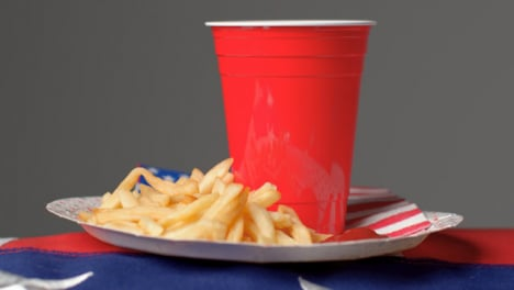 Close-Up-Shot-of-Rotating-Plate-of-Fries-with-Red-Plastic-Beer-Cup