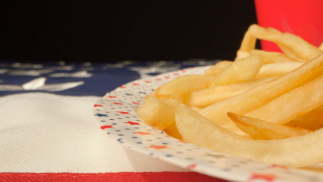 Sliding-Shot-Along-United-States-of-America-Flag-Past-Plate-of-Fries