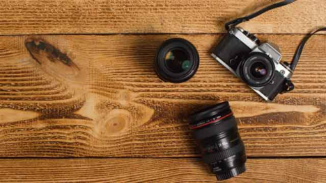 Top-Down-Shot-of-Person-Picking-Up-SLR-Camera-from-Table