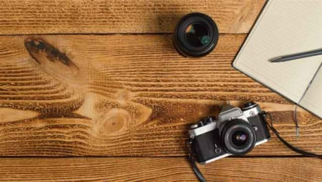 Top-Down-Shot-of-Person-Placing-SLR-Camera-On-Table-with-Left-Copy-Space