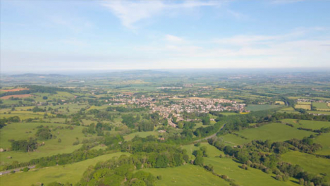 Drone-Shot-Flying-High-Over-Some-Countryside-Fields-Towards-a-Cotswold-Village