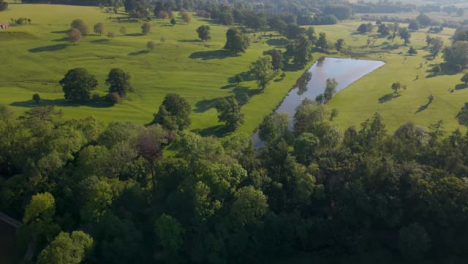 Drone-Shot-Approaching-Small-Body-of-Water-In-Cotswolds