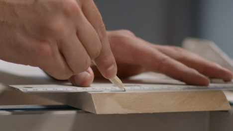 Close-Up-Shot-of-Hand-Using-Pencil-to-Mark-Cutting-Lines-On-Skirting-Board