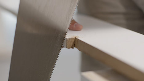 Close-Up-Shot-of-Hand-Saw-Being-Used-to-Cut-Skirting-Board