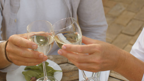 Close-Up-Shot-of-Middle-Aged-Couple-Bringing-Their-Wine-Glasses-Together