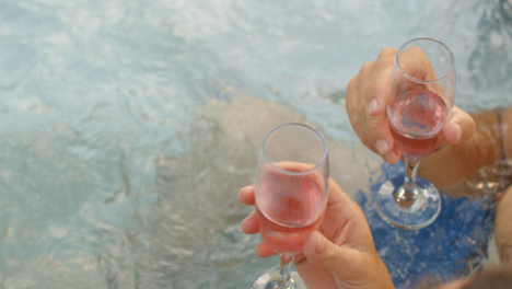 High-Angle-Shot-Looking-Down-On-People-Holding-Champagne-Glasses-In-Hot-Tub