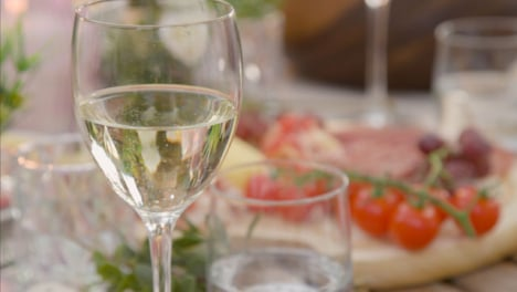 Pull-Focus-Shot-from-Alfresco-Dinner-Table-Spread-to-Glass-of-White-Wine