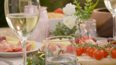 Pull-Focus-Shot-from-an-Alfresco-Dinner-Table-Spread-to-Glass-of-White-Wine