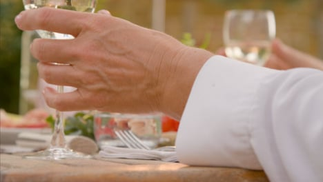 Pull-Focus-Shot-from-an-Alfresco-Dinner-Spread-to-Glass-of-White-Wine-Being-Place-On-Table
