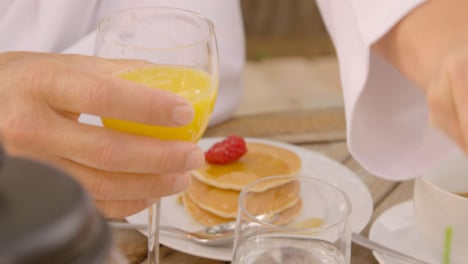 Tracking-Shot-Following-Glass-of-Orange-Juice-as-Middle-Aged-Man-Sips-It