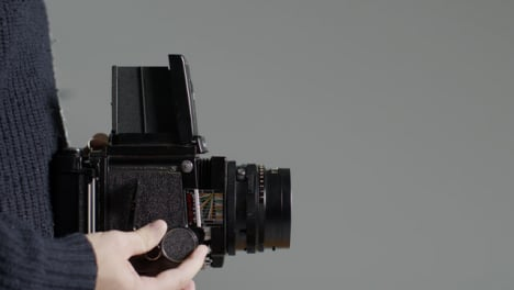 Side-Profile-Shot-of-Persons-Hands-Holding-Mamiya-RB67-and-Taking-Photo