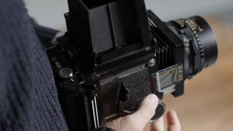 High-Angle-Shot-of-Persons-Hands-Holding-Mamiya-RB67-and-Taking-Photo