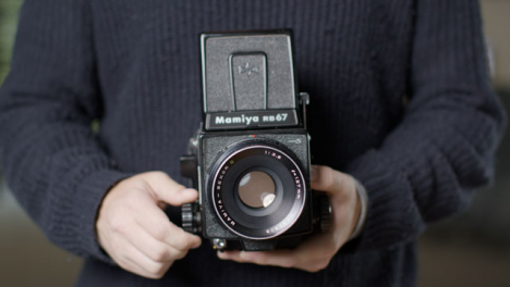 Close-Up-Shot-of-Persons-Hands-Holding-Mamiya-RB67-and-Taking-Photo