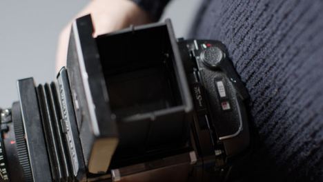 High-Angle-Shot-of-a-Persons-Hands-Holding-Mamiya-RB67-and-Taking-Photo