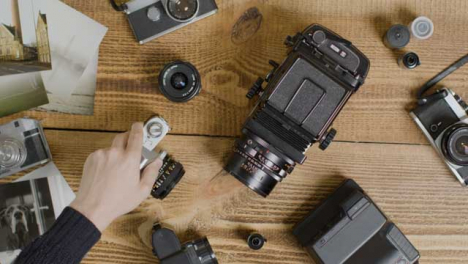Top-Down-Shot-of-a-Persons-Hands-Placing-Vintage-Film-Camera-On-Table