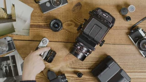 Top-Down-Shot-of-Photographers-Hand-Deciding-What-Vintage-Camera-to-Use
