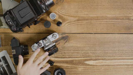 Top-Down-Shot-of-Photographer-Deciding-What-Camera-to-Use-with-Right-Copy-Space