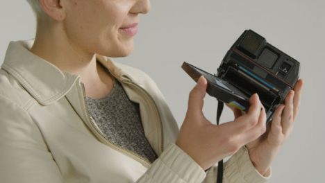 Side-view-of-a-female-photographer-loads-instant-film-camera