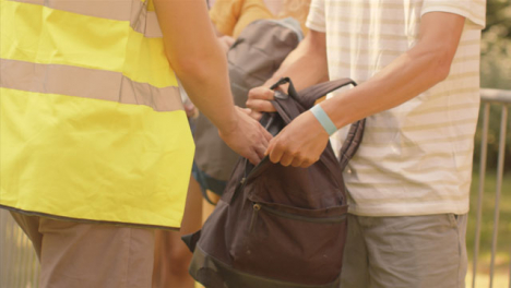 Tracking-Shot-of-Festival-Goers-Showing-Security-Guard-Bags-During-a-Bag-Check