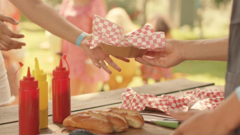Close-Up-Shot-of-Fast-Food-Stand-Worker-Passing-Hot-Dog-to-Festival-Goer