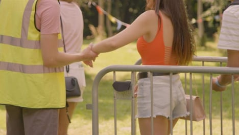Sliding-Shot-of-Festival-Goers-Getting-Wrist-Bands-Checked-at-Security-Barrier