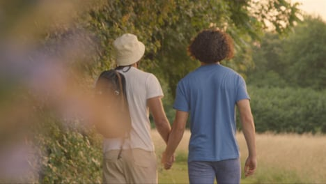 Pull-Focus-Shot-of-Same-Sex-Couple-Walking-Along-Country-Path