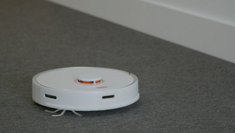 Close-Up-Shot-of-Robotic-Vacuum-Cleaner-Cleaning-a-Carpet