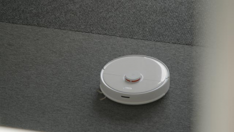 High-Angle-Shot-of-a-Robotic-Vacuum-Cleaner-Cleaning-a-Carpet