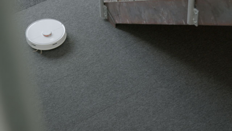 High-Angle-Shot-of-a-Automatic-Robotic-Vacuum-Cleaner-Cleaning-Carpet