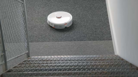 High-Angle-Shot-Down-Stairs-of-Robotic-Vacuum-Cleaner-Cleaning-Carpet