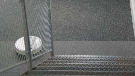High-Angle-Shot-Down-Stairs-of-a-Robotic-Vacuum-Cleaner-Cleaning-Carpet
