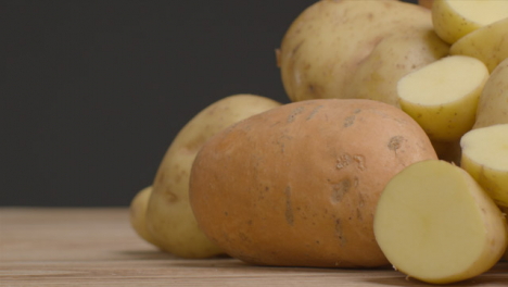 Sliding-Shot-Revealing-Assorted-Potatoes-On-Rustic-Wooden-Table-02