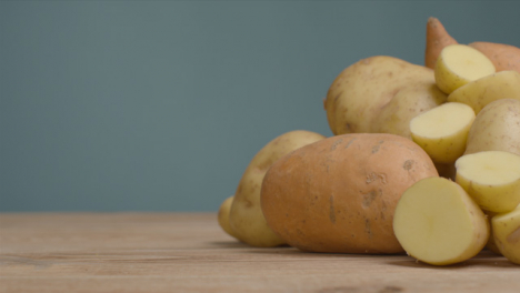 Sliding-Shot-Revealing-Assorted-Potatoes-On-Rustic-Wooden-Table-04