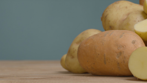 Sliding-Shot-of-Assorted-Potatoes-On-a-Rustic-Wooden-Table