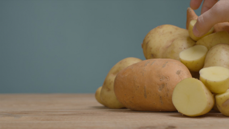 Close-Up-Shot-of-Pile-of-Assorted-Potatoes-as-Hand-Takes-One-Away