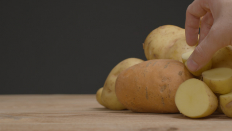 Close-Up-Shot-of-Pile-of-Assorted-Potatoes-as-Hand-Takes-Two-Away