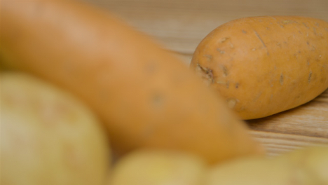 Pull-Focus-Shot-of-Potatoes-On-Rustic-Wood-Table