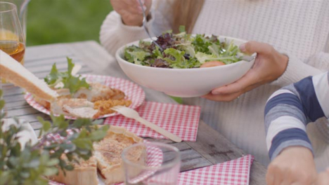 Tracking-Shot-Over-Table-of-Food-as-Family-Serve-It-Up-During-Outdoor-Dinner-01