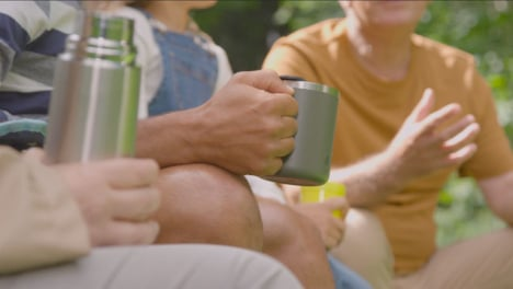 Pull-Focus-Shot-of-People-Holding-Drinks-On-Camping-Trip-01