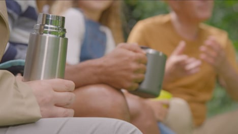Pull-Focus-Shot-of-People-Holding-Drinks-On-Camping-Trip-02