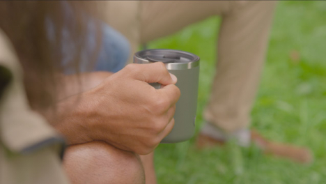 Over-the-Shoulder-Shot-of-Hand-Holding-Cup-On-Camping-Trip
