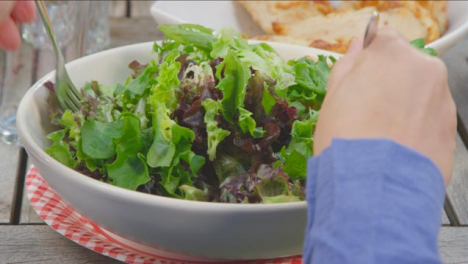 Over-the-Shoulder-Shot-of-Woman-Placing-Serving-Spoons-In-Salad-Bowl