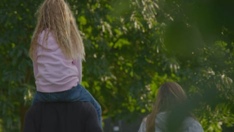 Long-Shot-of-Young-Girl-Sitting-On-Her-Father-s-Shoulders
