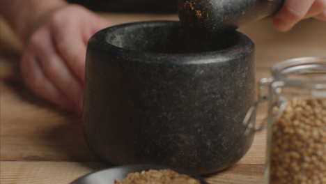 Close-Up-Hand-Using-Mortar-and-Pestle-to-Grind-Cumin-Spice
