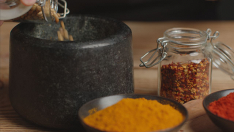 Tracking-In-Shot-Picking-Up-Cumin-to-Mortar-and-Pestle-on-Table