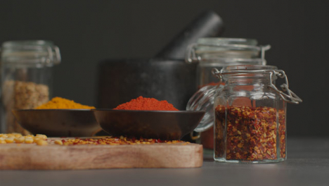 Sliding-Shot-of-Spices-and-Grains-on-Black-Worktop-02