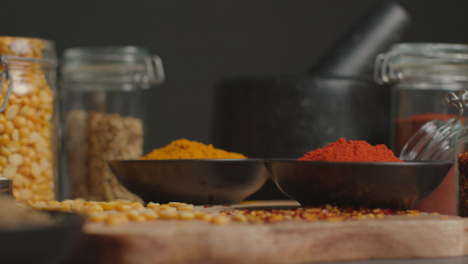 Tracking-In-Shot-of-Spices-and-Grains-on-Black-Worktop