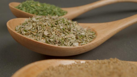Extreme-Close-Up-Tracking-Out-Shot-of-Herbs-and-Spices-in-Wooden-Spoons