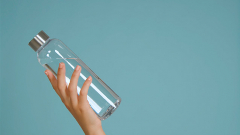 Close-Up-Shot-of-Young-Womans-Hand-Bringing-Water-Bottle-into-Frame-with-Copy-Space-01