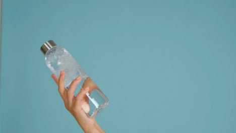 Close-Up-Shot-of-Young-Womans-Hand-Bringing-Water-Bottle-into-Frame-with-Copy-Space-02
